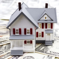 home equity concept - house on top of pile of money