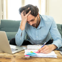 Angry man paying bills and debts in home with laptop and calculator