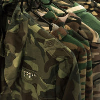 Multiple military jackets hanging on clothes rack