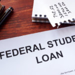 Federal student loan form on a table surrounded by office supplies