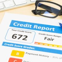 Fair credit score report with pen and keyboard; document is mock