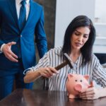 Worried woman holding hammer above piggy bank at table near collector with outstretched hand in room