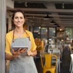 Small business owner at entrance looking at camera