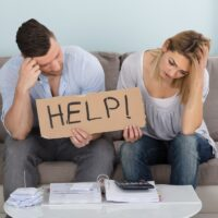 Worried Couple Holding Help Sign While Calculating Bills
